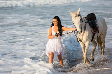 young woman walking with horse on beach