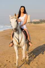 happy young woman riding a horse on beach