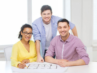 three smiling architects working in office