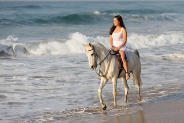 young lady riding horse on beach