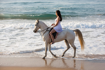 side view of young woman horse ride on beach