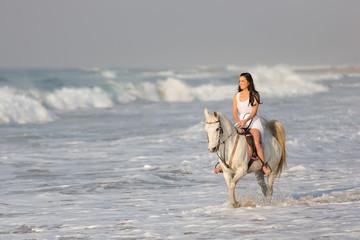 beautiful woman riding horse on beach