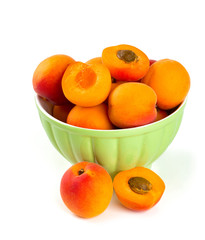 fresh apricots in a bowl over white