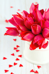 bouquet of red tulips in a pitcher and scattered wooden hearts