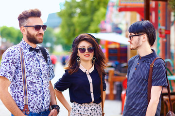 stylish friends talking on city street