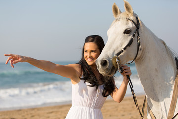 happy woman pointing at distance with her horse