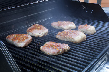 Beef steaks cooking on a grill