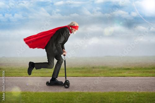 senior superhero riding a scooter - 66931106