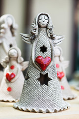 Ceramic angel with red heart on wooden table