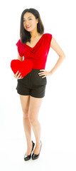 Young woman holding heart shape cushion and smiling