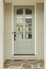 Light green front door to white brick home