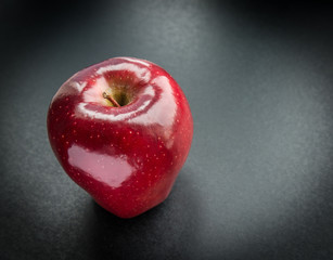 Dark-red apple on gray background. Selective focus.