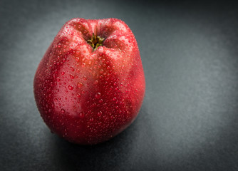 Dark-red apple with water drops. Selective focus.