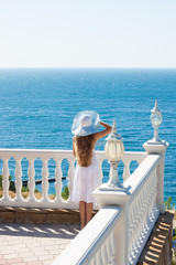 Young girl on the white background of the sea on the terrace