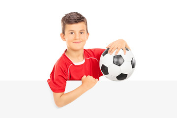 Kid holding a football behind a blank panel
