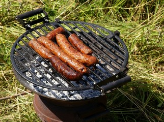 grilled sausages upon heat ash
