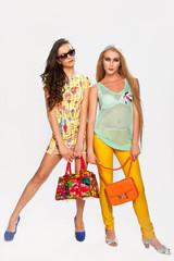 Две модные девушки с сумками на белом фоне