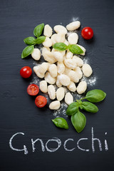 Above view of raw gnocchi with tomatoes and green basil leaves