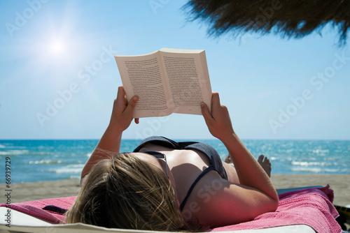 Leinwandbild Motiv Ein Buch am Strand lesen