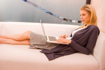 Smiling young woman using laptop sitting couch
