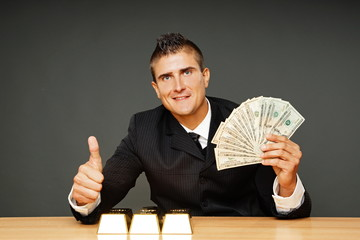 Young businessman in suit shows you money and thumb up