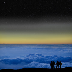 Group of climbers above the clouds but under the stars.