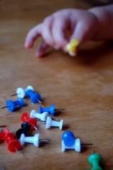 Kinderhand mit Pinnwandnadeln