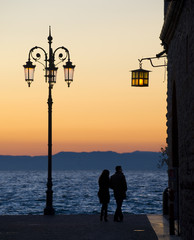 Silhouette of a couple on the shore of lake Garda, Italy.
