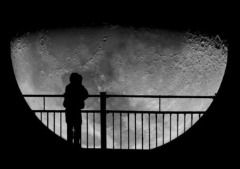 Silhouette of a child staring at the Moon. Science education.