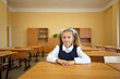 Little girl sits at wooden school desk in classroom at school.