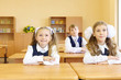 Two girls and boy in uniform sit at school desks in classroom