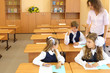 Two girls and boy sit at wooden school desks in classroom
