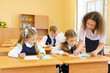 Two girls and boy write at school desks in classroom and teacher