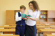 Boy with teacher stand in classroom and looks at exercise book