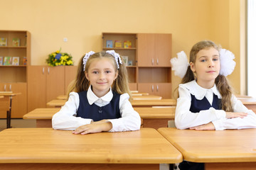 Two happy girls in uniform sit at wooden school desk