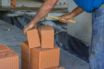 Builder worker cutting a clay block with brick hammer