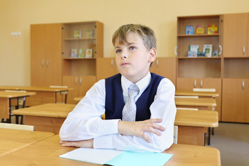 Boy sits at desk in classroom and listens attentively to teacher