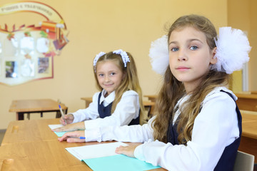 Two girls in school uniform sit at wooden school desk