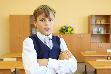 Boy with crossed arms stands in empty classroom and looks