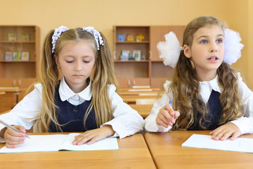 Two girls in uniform sit at wooden school desk