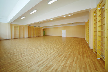Empty school gymnasium floor with yellow and climbing near walls