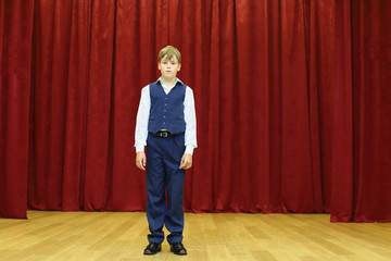 Serious boy in suit with vest stands on stage with red curtains.