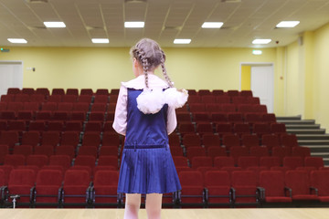 Back of girl with braids and bows standing on stage