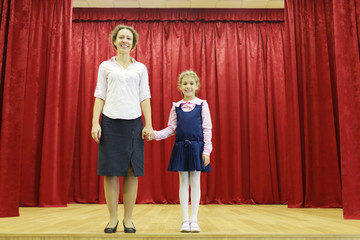 Happy mother and daughter stand on stage with red curtains