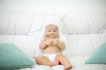 Barefoot little kid in white soft pants and hat sits