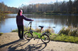 Back of woman standing with bicycle near lake with ducks in park