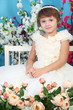 Cute little girl in white dress sits on bench among flowers.