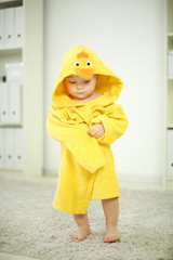 Little cute baby in yellow robe stands on carpet