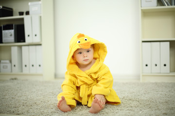 Little cute baby in yellow robe sits on white carpet and looks
