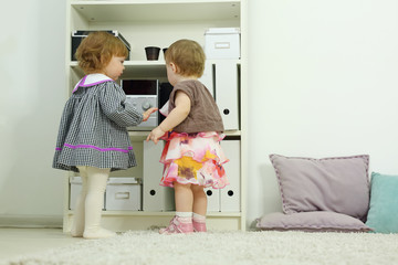 Two happy little girls stand near shelves
